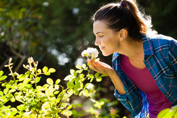 smiling woman smelling roses at backyard