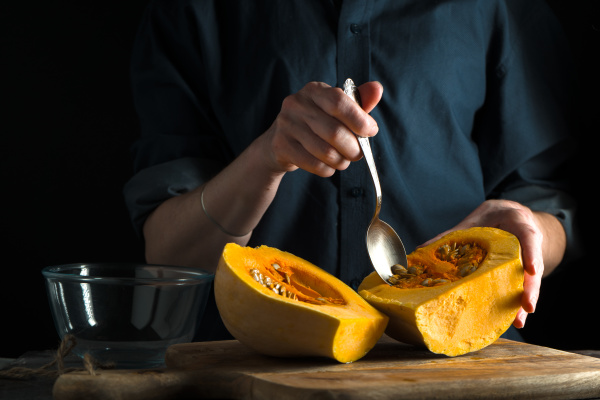 spoon in hand pumpkin halves