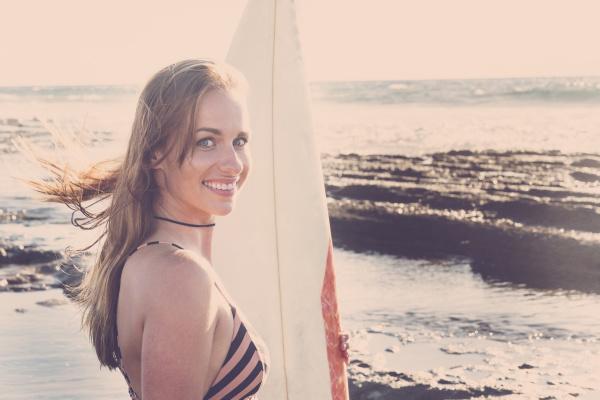 caucasian woman standing on beach holding