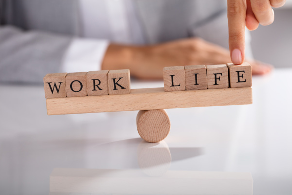 businesspersons finger showing imbalance between work