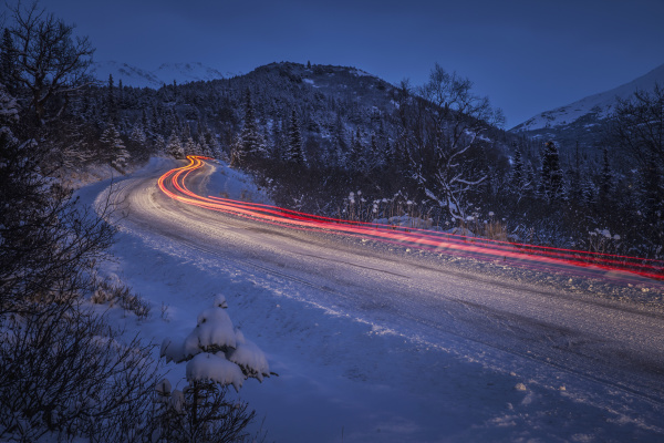 vehicle taillight trails on a snowy