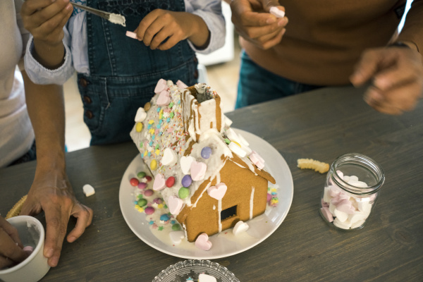 family pasting gingerbread house in kitchen