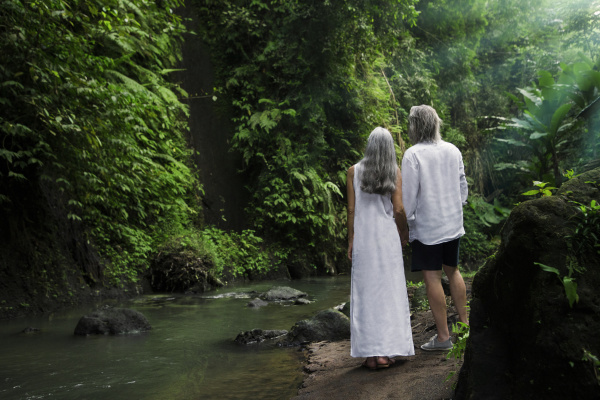 handsome senior couple in tropical waterfall
