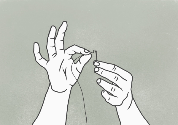 cropped image of woman threading needle