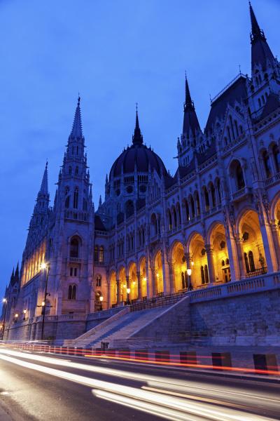 illuminated hungarian parliament and light trails