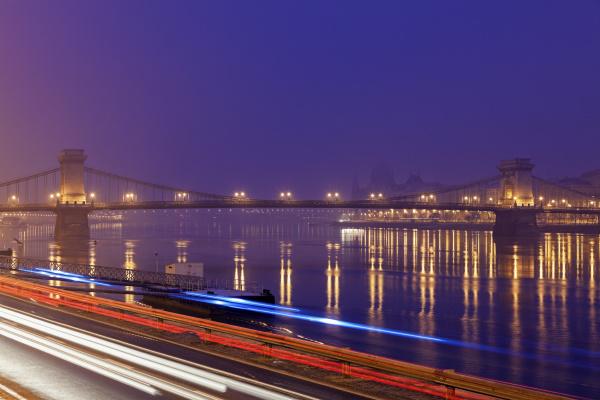 illuminated chain bridge and light trails