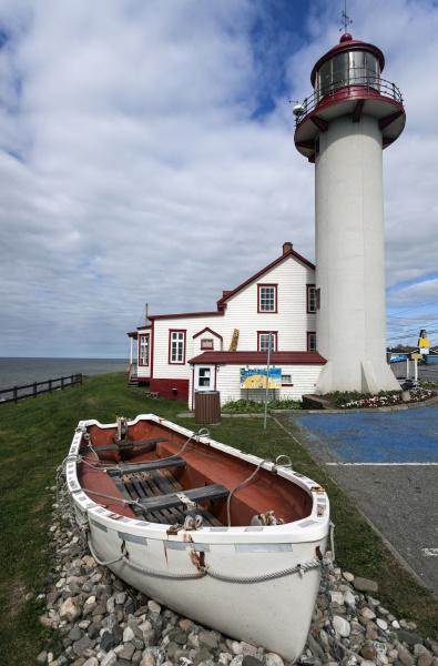 matane lighthouse and empty white rowboat