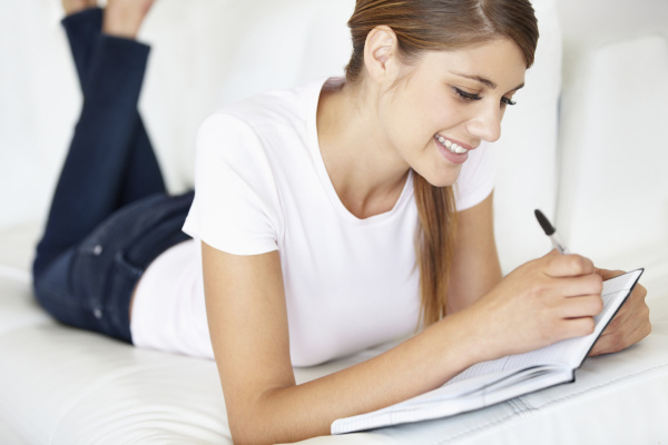 young woman writing in notepad