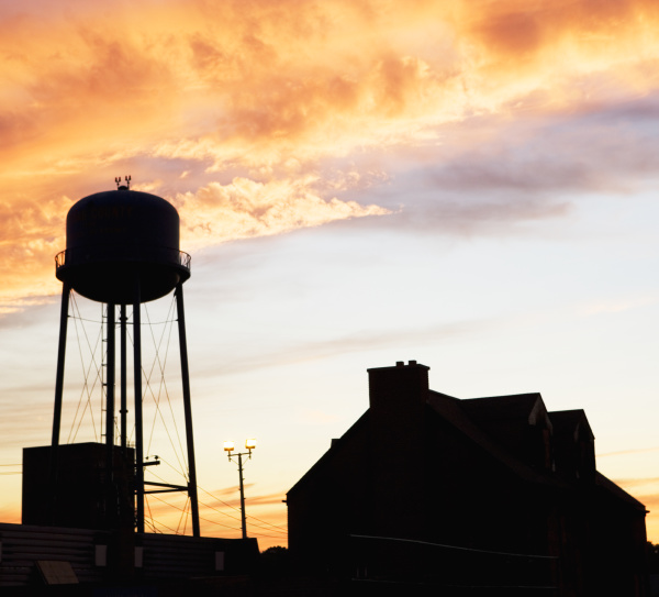 water tower and house against sunset