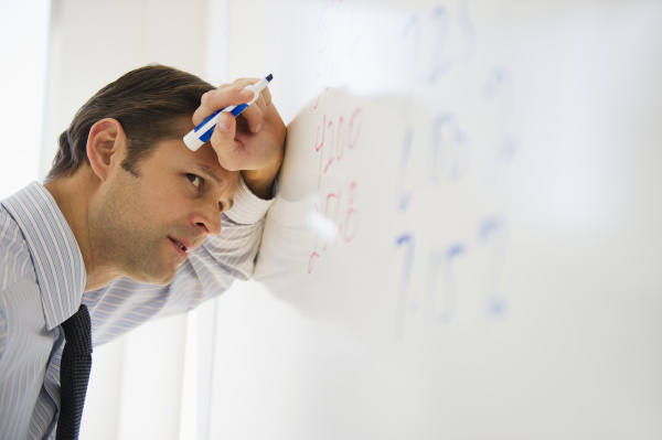 exhausted man leaning against whiteboard