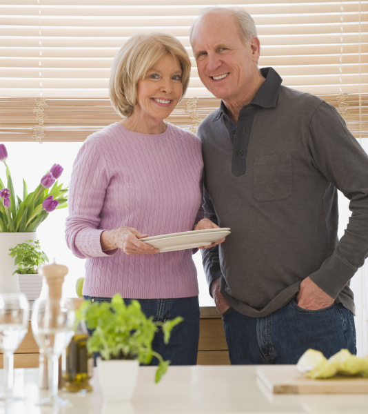 senior couple with dishes in kitchen