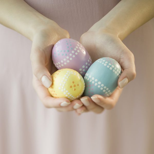 woman holding decorated eggs