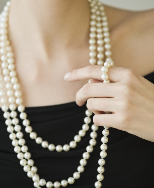 woman wearing strands of pearls