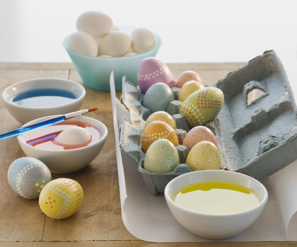 decorated eggs next to bowls of