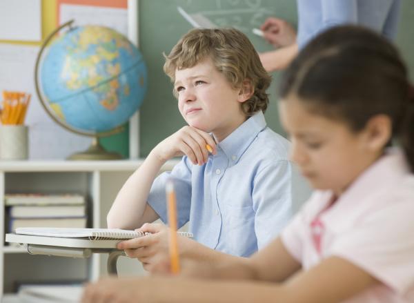 boy thinking at school desk