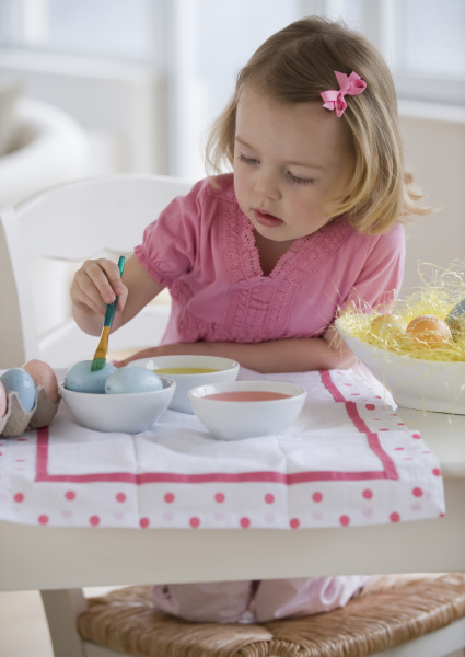 young girl decorating eggs