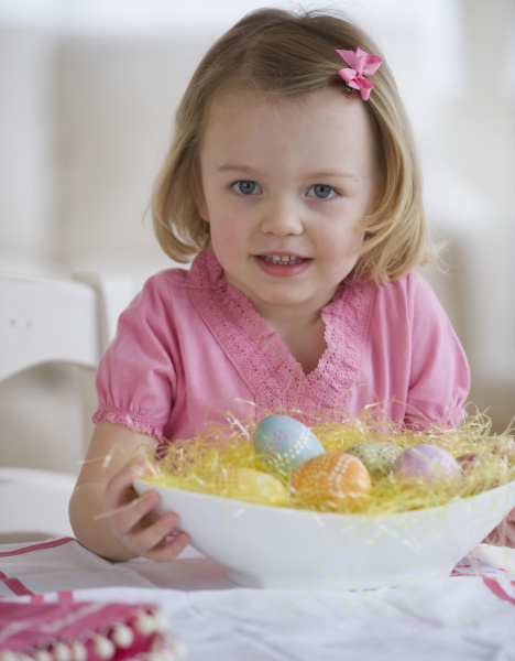 young girl holding bowl of easter
