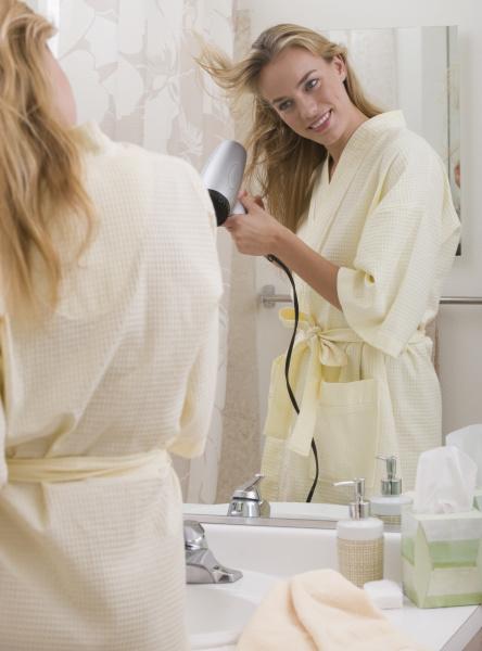 woman blow drying hair in bathroom