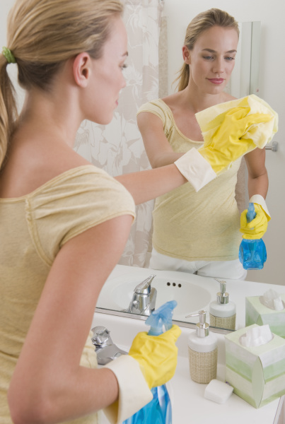 woman cleaning mirror in bathroom
