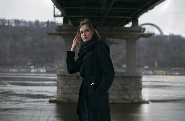 caucasian woman standing under bridge near