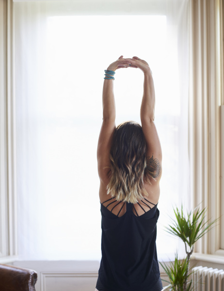 woman practicing yoga stretching arms