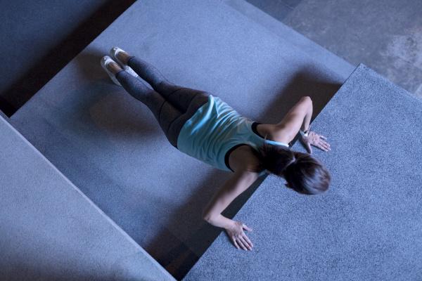young woman doing pushups in modern