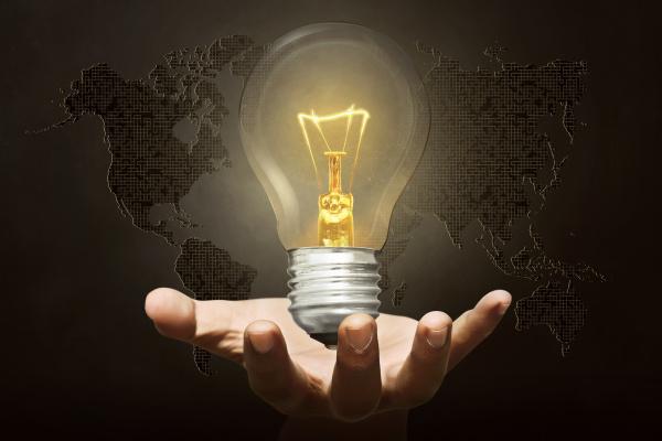 human hand holding glowing lights bulb