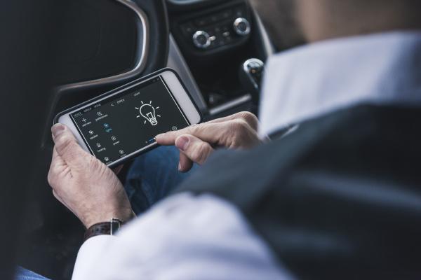 man in car adjusting smart home