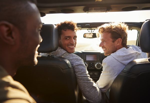 three young adult men driving with
