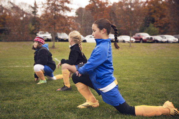 team players exercising on soccer field
