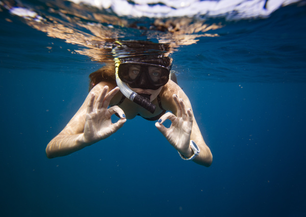 young woman gesturing while snorkeling undersea