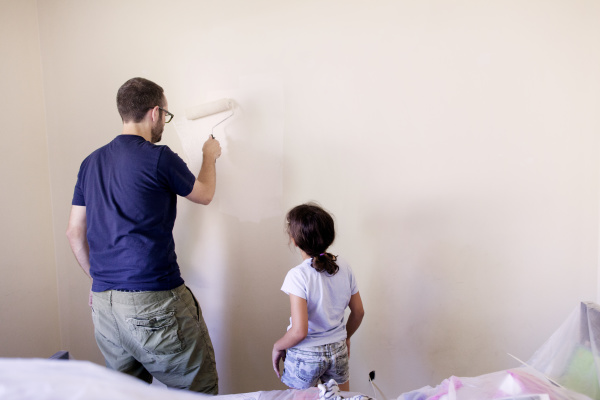 girl looking at father painting wall