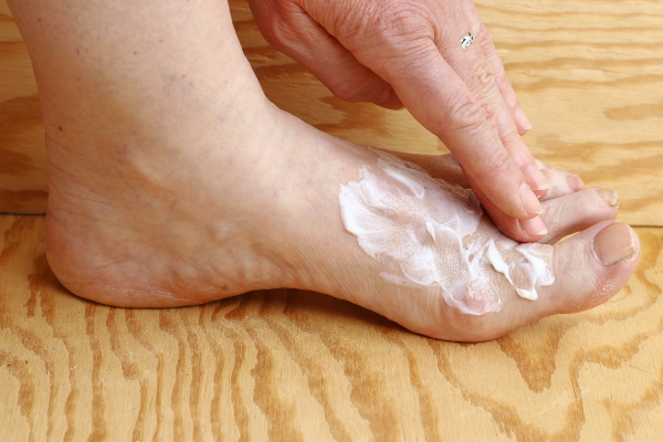 a woman creams her foot in
