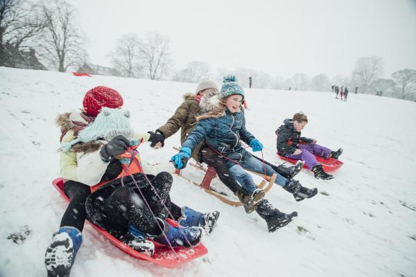 children having a sledding race