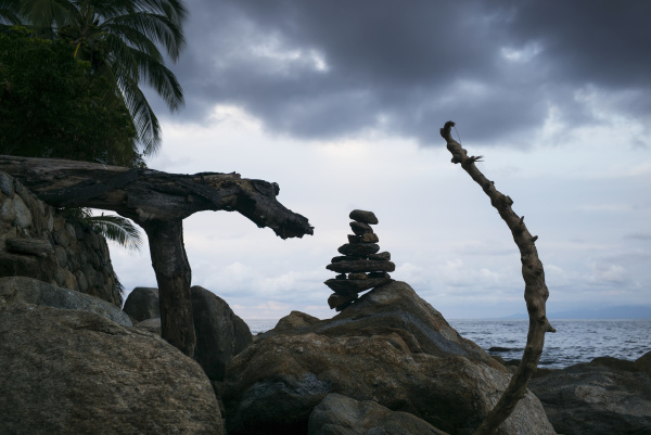 inuksuk and tree branches on boulders