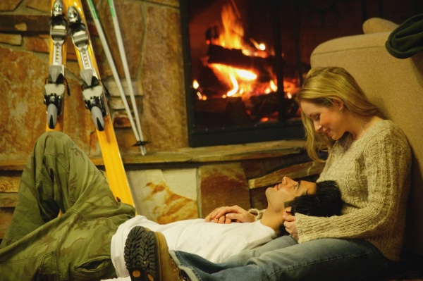 couple relax by fireplace