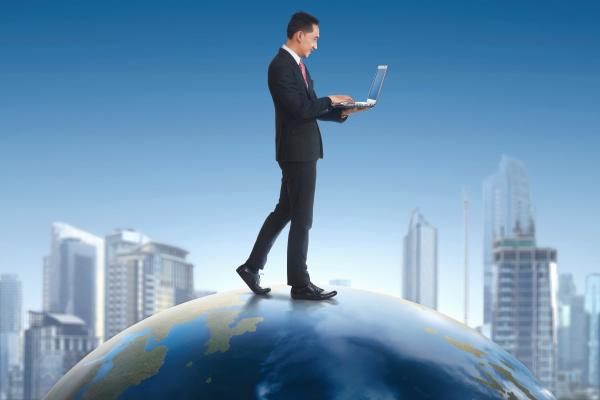 asian businessman holding laptop while walking