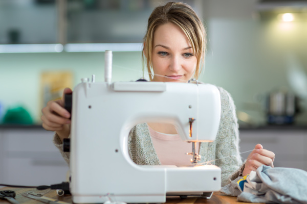 pretty young woman sewing clothes