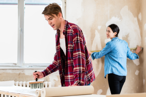 young man applying adhesive to wallpaper