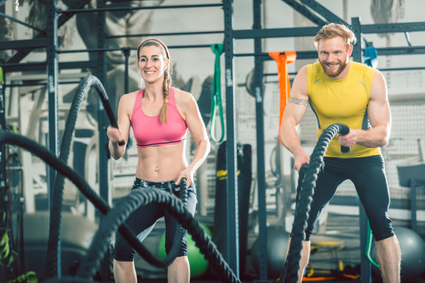 strong couple exercising together with battle