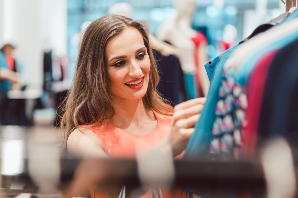 woman browsing through dresses on rack
