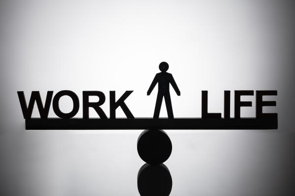 human figure standing between work and
