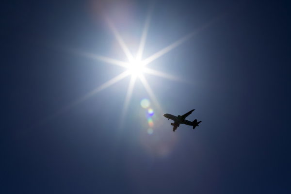 silhouette of airplane against a sunburst