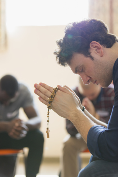 serene man praying with rosary in