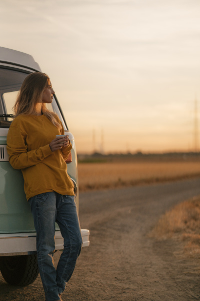 young woman standing at camper van