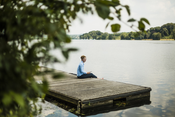 woman sitting on jetty at a