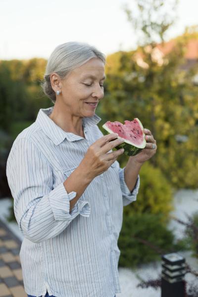 senior woman eating watermelon slice in