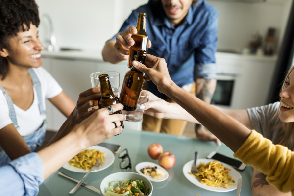 cheerful friends clinking beer bottles at