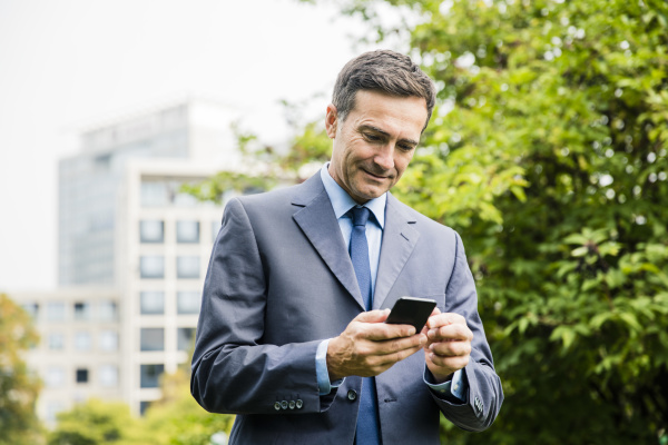 businessman using cell phone in city