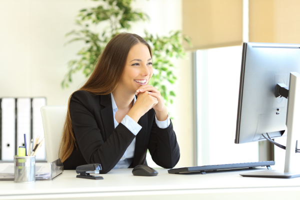 businesswoman looking attentive to pc monitor